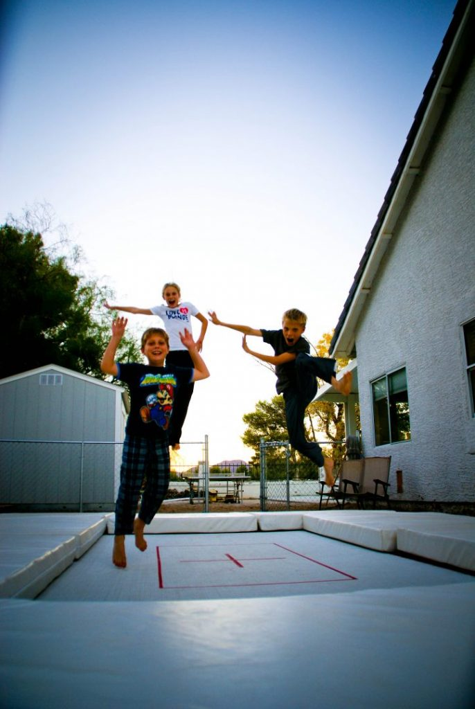 A family bouncing on a MaxAir Trampoline in their backyard.