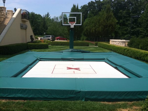 An example of a MaxAir Trampolines residential tramp with a basketball hoop setup.