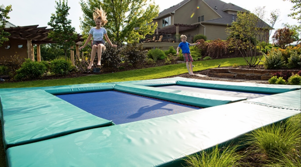 A pair of kids jumping on a completed in-ground trampoline.
