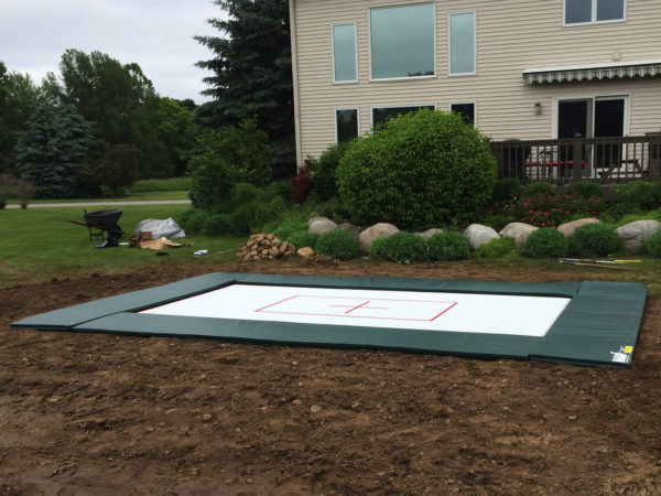 The backyard is the perfect trampoline location for your home, but there are other options. An in-ground trampoline 6x12 newly installed behind a suburban house.
