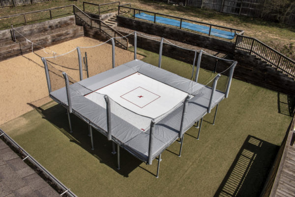 An outdoor trampoline used for fitness and training. Gray, above ground, with safety nets