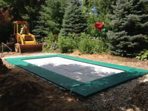 MaxAir will help you find an installer that nows how to put a trampoline in the ground. A dozer sits next to a finished trampoline pit.